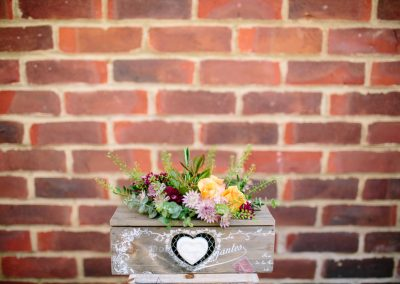 box of pretty flowers on a stand against a brick wall