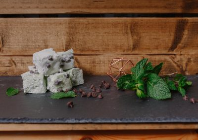 Mint choc chip marshmallows on display on a slate board in front of a rustic wood wall