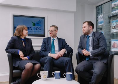 three estate agents sitting together in an informal meeting