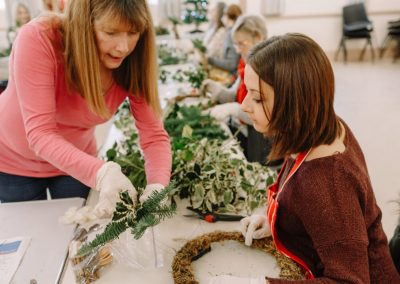 woman teaches girl how to make a Christmas wreath