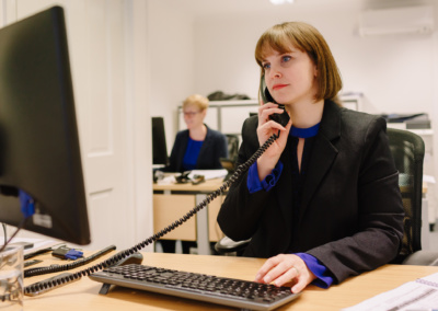 Woman sits on phone in office