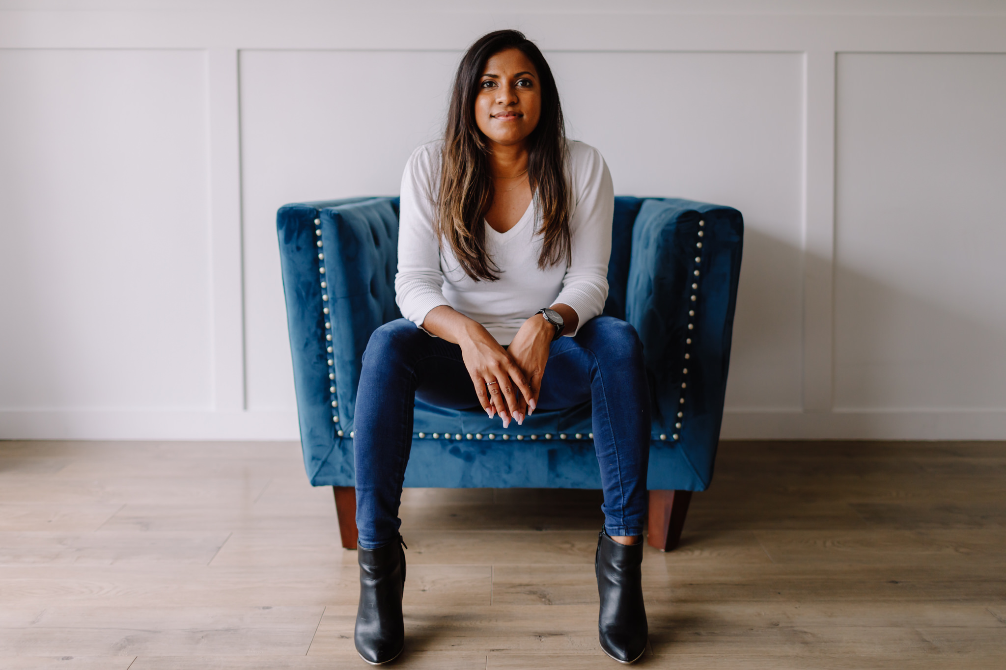 Woman sits on blue chair and looks into camera