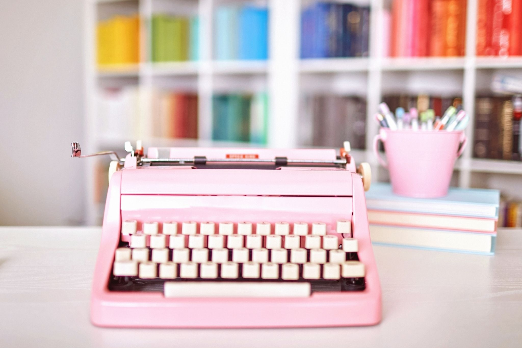 pink typewriter on desk in front of rainbow coloured shelving